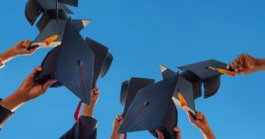 Students holding graduation caps