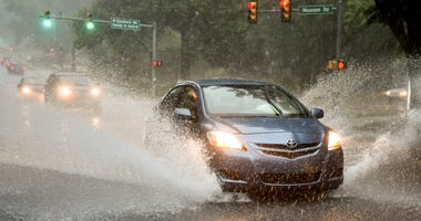 Cars drive through flooded streets