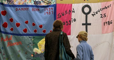 Visitors look at panels of the AIDS Memorial Quilt that are being displayed on February 13, 2012 in San Francisco, California.