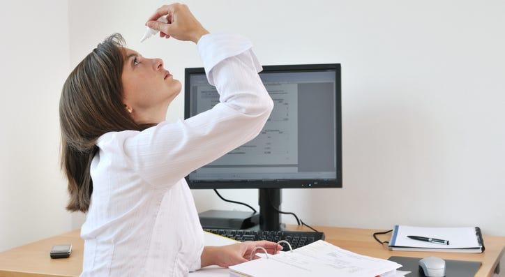 A person using eye drops.