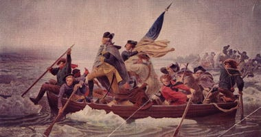 General George Washington (1732 - 1799) stands in the prow of a rowing boat crossing the Delaware to seek safety in Pennysylvania after defeat by the British.