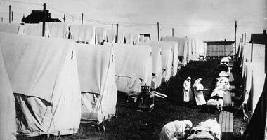 Nurses care for victims of a Spanish influenza epidemic outdoors amidst canvas tents during an outdoor fresh air cure, Lawrence, Massachusetts, 1918.