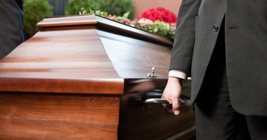 Funeral with casket carried by pallbearer