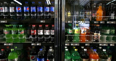 Various bottles of soda are displayed in a cooler.