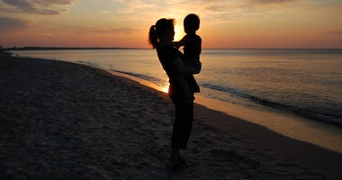 Mother and child on a beach at dusk