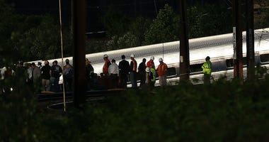 Investigators and first responders work near the wreckage of an Amtrak passenger train carrying more than 200 passengers from Washington, DC.
