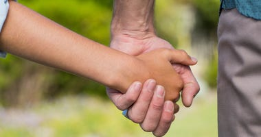 An adult holding a child's hand.