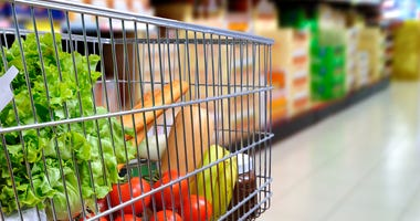 A grocery cart full of food.