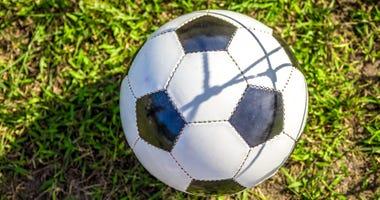 Soccer ball on grass pad.
