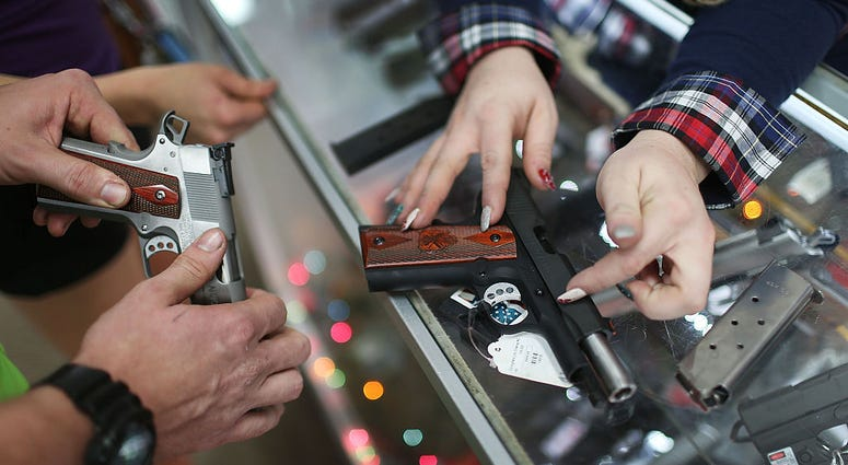 POMPANO BEACH, FL - DECEMBER 23: A customer compares handguns before buying one as a Christmas present at the National Armory gun store on December 23, 2015 in Pompano Beach, Florida.