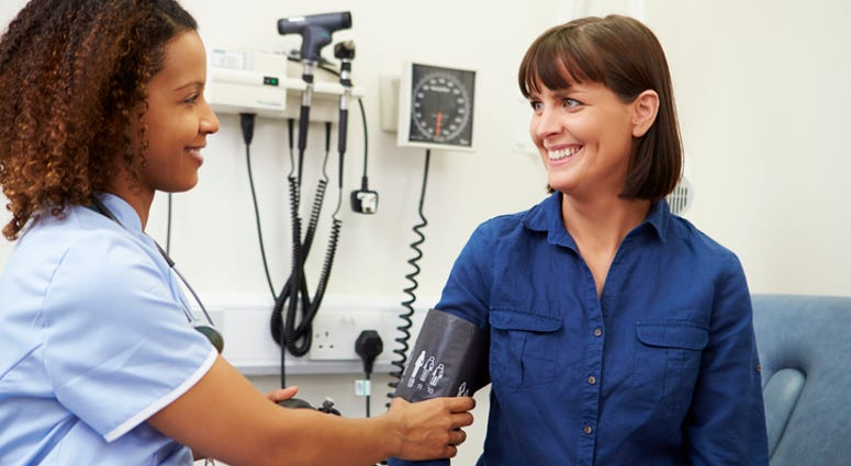 A woman getting her blood pressure checked by a doctor.