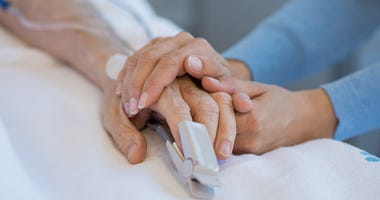 Person holding hands with a hospital patient.