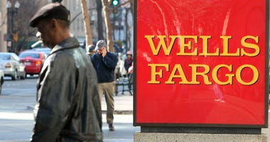 A pedestrian walks by a sign outside of a Wells Fargo bank branch.