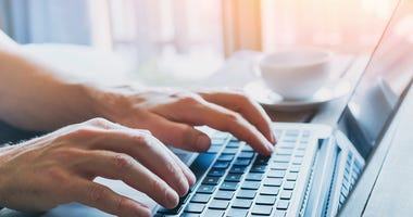 A person typing on their laptop.