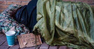 A homeless female veteran sleeping on the ground.