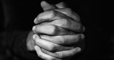 Man with his hands clasped.