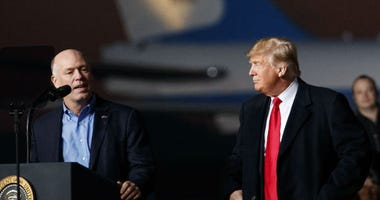 Rep. Greg Gianforte, R-Mont., speaks as President Donald Trump stands right during a campaign rally at Minuteman Aviation Hangar, Thursday, Oct. 18, 2018, in Missoula, Mont.