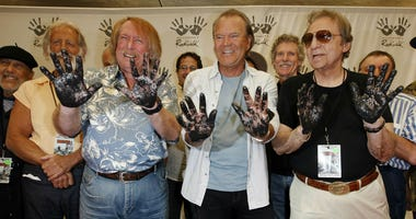 In this June 25, 2008, file photo, Don Randi, from left, Glen Campbell and Hal Blaine, representing session musicians known as The Wrecking Crew, place their hands in the cement following the induction ceremony for Hollywood's RockWalk in Los Angeles.