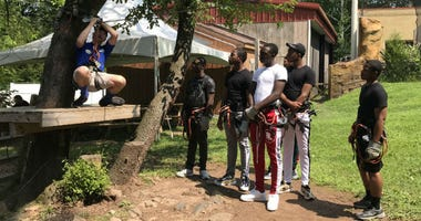 Students from the Glen Mills Schools learn how to zip line during a trip to the Elmwood Park Zoo.