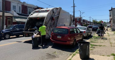 A sanitation truck collects trash near 58th and Arch Streets in West Philadelphia.