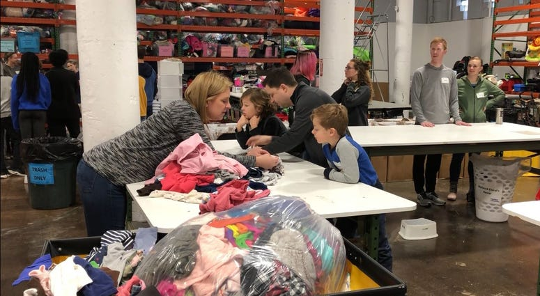 Families spend their day volunteering for Cradles to Crayons in East Falls, assembling care packages for children in need.