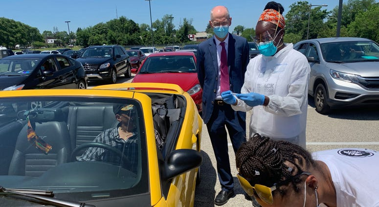 Philadelphia Health Commissioner Dr. Thomas Farley watches as Dr. Ala Stanford and an aide conduct COVID-19 testing at Enon Tabernacle Church.