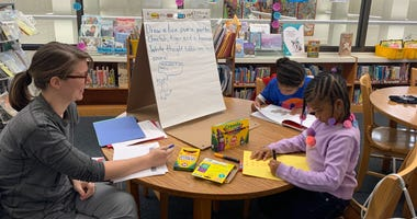 Megan Larson of the Free Library's Literacy Lab works with two young children to help them with their reading.