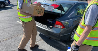 Philabundance volunteers give food to people waiting in the drive-thru line