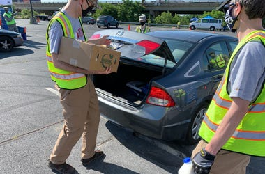 Philabundance volunteers give food to people waiting in the drive-thru line