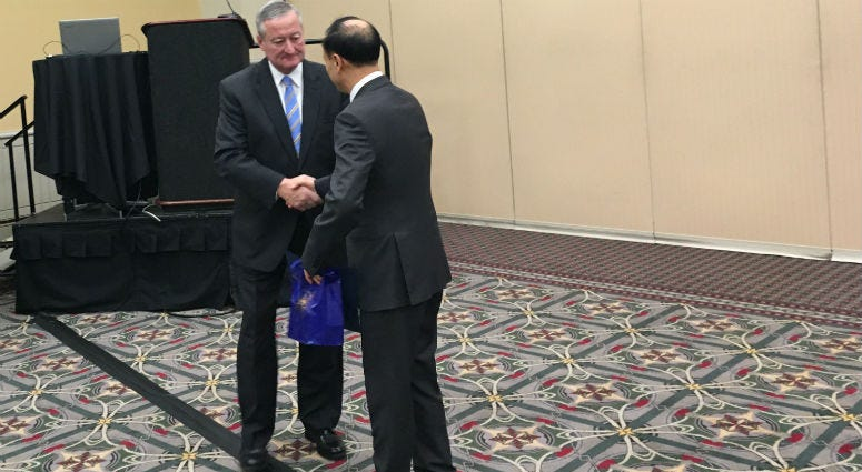 Mayor Jim Kenney stands at the podium as Chinese attendees look on and Kenney shakes hands with Heyi Song, chief editor of Chinese Media Group
