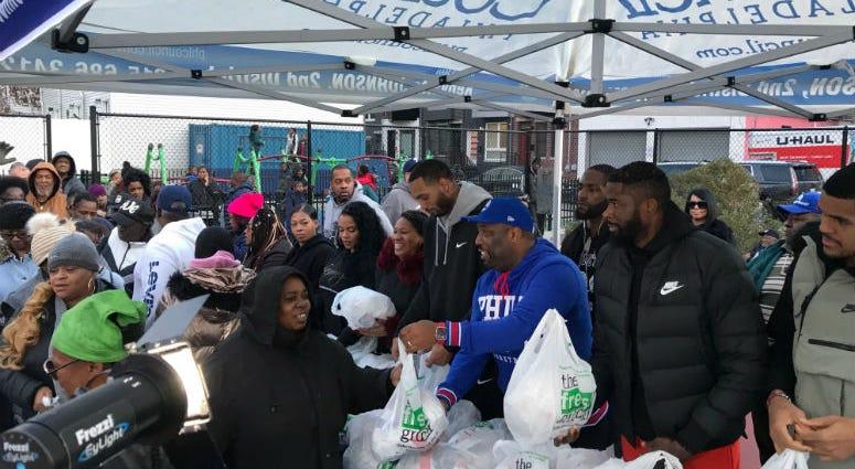 Philadelphia 76ers' Tobias Harris, Mike Scott, and James Ennis III giving out turkeys in South Philadelphia.