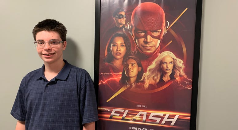 """Michael stands next to a promotional poster for his favorite TV show, """"The Flash,"""" at the KYW broadcast center."""