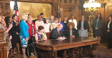 Gov. Tom Wolf signs the executive order in his reception room.