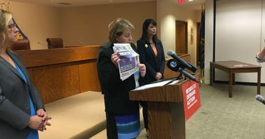 Kathy Stone, executive director of the Domestic Abuse Project of Delaware County, holds a recent newspaper detailing an account of domestic abuse involving use of a firearm.