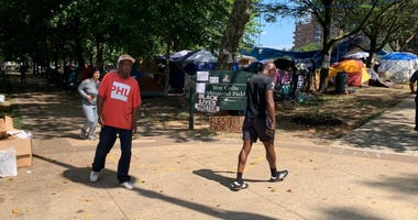 The tent encampment at Von Colln Field on the Benjamin Franklin Parkway doubles as a protest for homeless rights, but neighbors have raised concerns over sanitation.