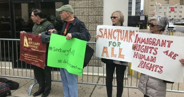 More than a dozen people stood in solidarity with religious leaders and participated in a prayer meeting in front of the Immigration Customs Enforcement building in Center City.
