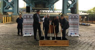Officials from the Philadelphia Parking Authority and the Delaware River Port Authority break ground on the future city of a 200-space parking lot under the Benjamin Franklin Bridge.