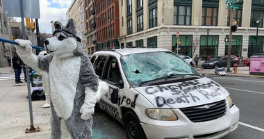 A protester dressed in a dog costume helps destroy a Chrysler minivan, as a statement regarding the company's support of the Iditarod sled dog race.