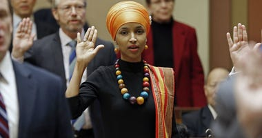 In this Tuesday, Jan. 3, 2017 file photo, State Rep. Ilhan Omar takes the oath of office as the 2017 legislature convened in St. Paul, Minn.