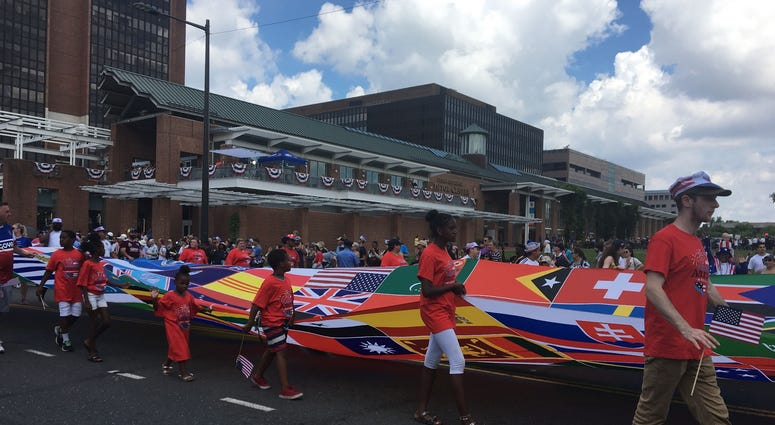 A banner representing the flags of the world marches by in the 2019 Independence Day Parade.