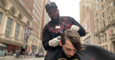 Brennon Jones gives a free haircut in Center City, on the median at Broad and Walnut Streets.