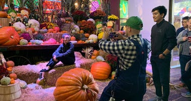 Festival-goers taking pictures with a variety of giant pumpkins and plants at the Reading Terminal Market Harvest Festival.