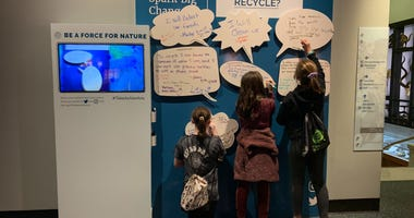 A group of kids write down what they changes they plan to make to positively affect the environment at the Academy of Natural Sciences.