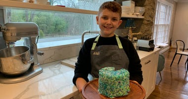 Haverford preteen Avner Schwartz shows a cake he baked.