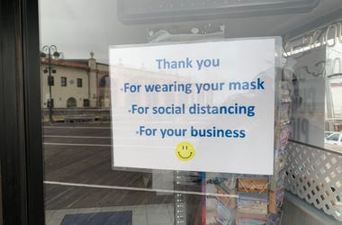 A sign on a business door reminding people to wear masks