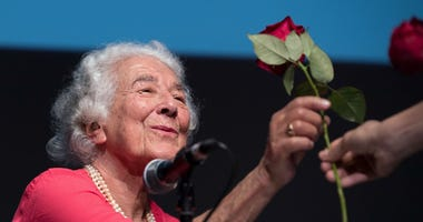 "In this Sept. 15, 2016 file photo British writer Judith Kerr holds a rose in Berlin, Germany. Judith Kerr, author and illustrator of the bestselling ""The Tiger Who Came to Tea"" and other beloved children's books, has died at the age of 95."