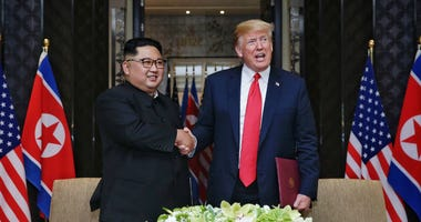 Kim Jong Un shakes hands with Donald Trump