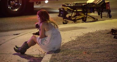 In this Oct. 2, 2017 file photo, a woman sits on a curb at the scene of a shooting outside a music festival on the Las Vegas Strip. It took 11 minutes for the gunman in the deadliest mass shooting in modern U.S. history to kill 58 people.