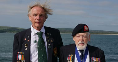 Former Royal Marine Les Budding, right, stands with Philip Collins, 62, who is the son of the late F.E. Collins of 45 Commando, who fought alongside Budding on D-Day, as they pose for a photo aboard the MV Boudicca ship.