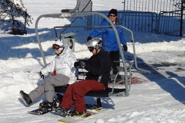 A ski lift attendant helps skiers on and off.